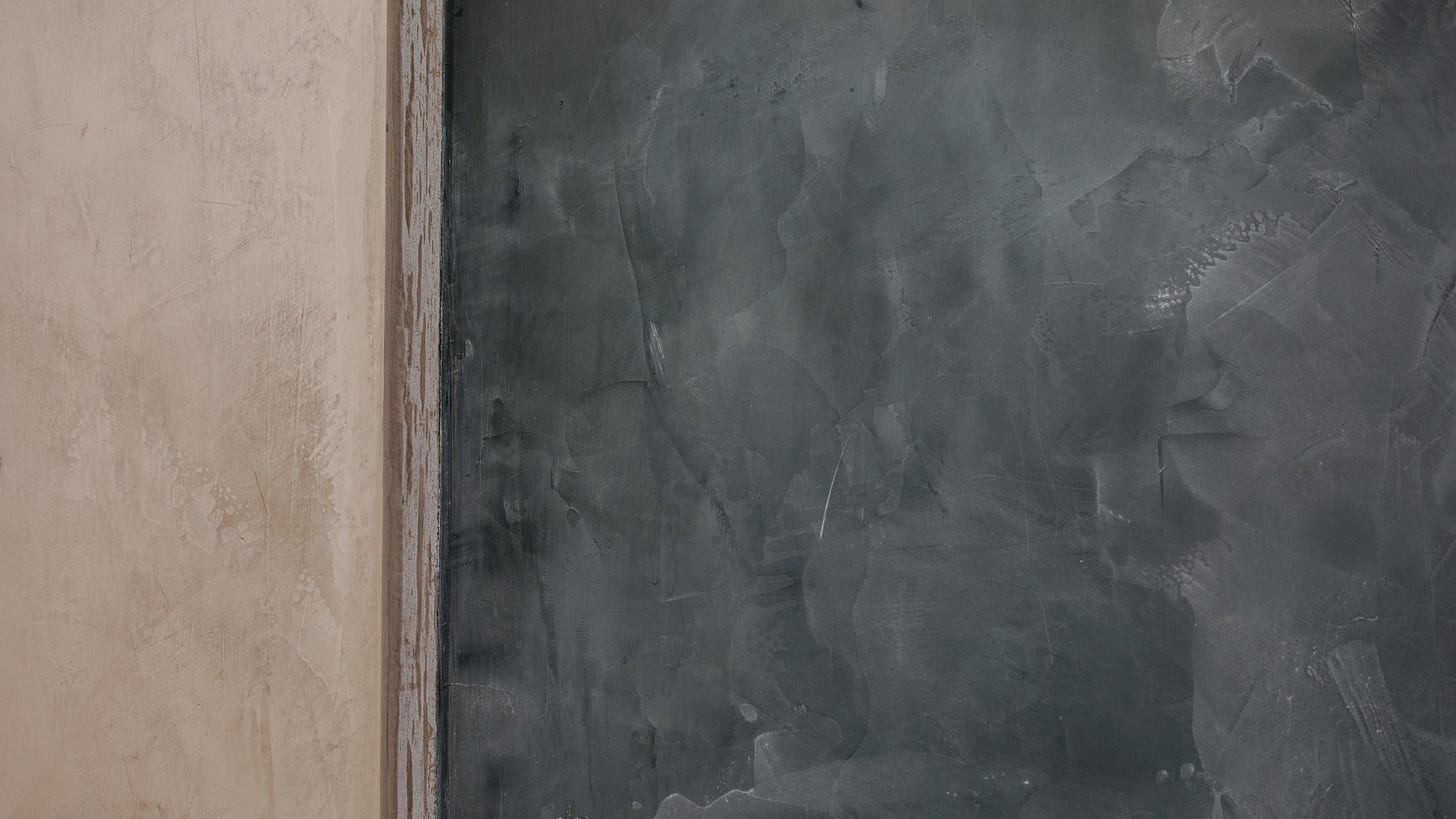 Color photograph of an empty chalkboard mounted on a wall. Only a portion of the chalkboard is visible.