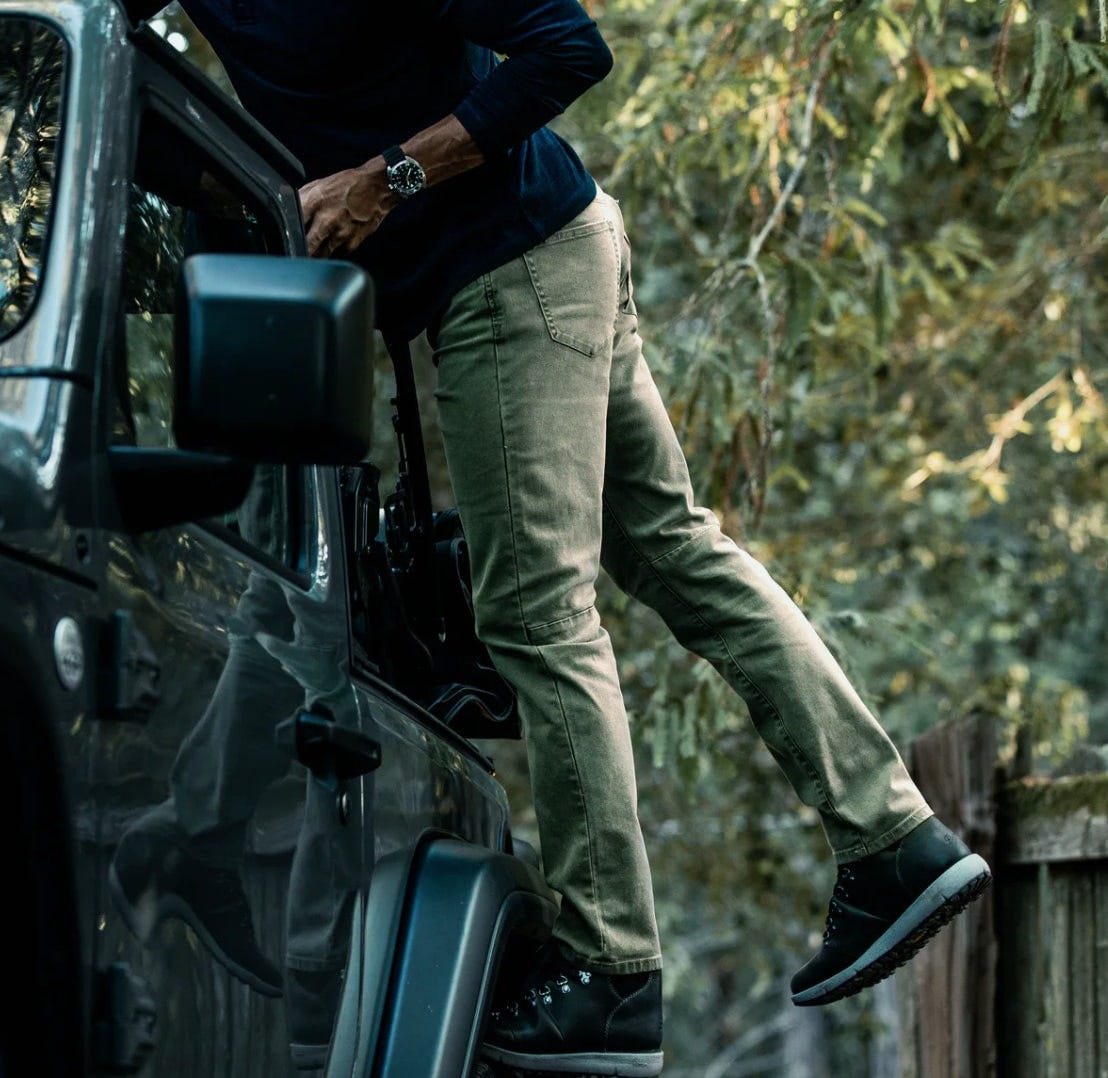 a man wears the proof rover pants while reaching onto the roof of his jeep