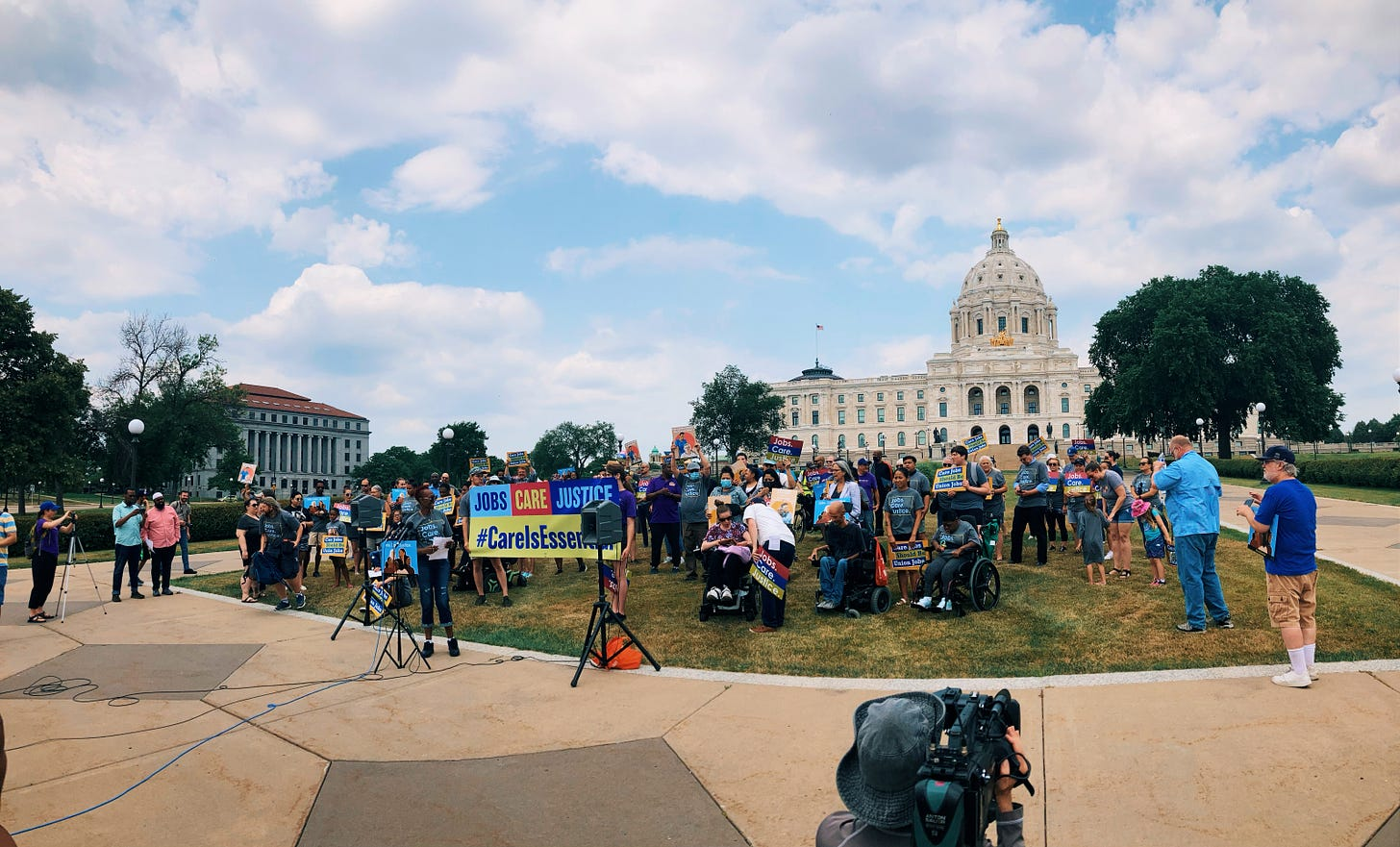 """a crowd gathers on the front lawn of the state capitol building with signs saying """"jobs care justice"""" as a newsperson points their camera at them"""