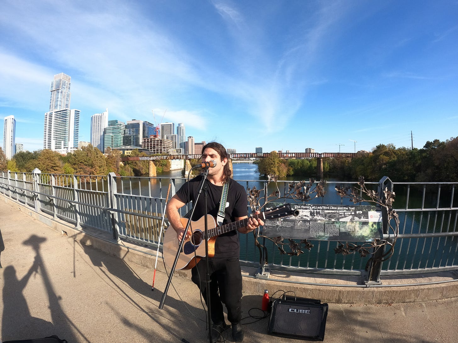 anthony standing on the bridge holding his guitar playing it with his white cane in the background and the city of austin texas in the background there is a river below him and the sky is blue and its nice and hot outside