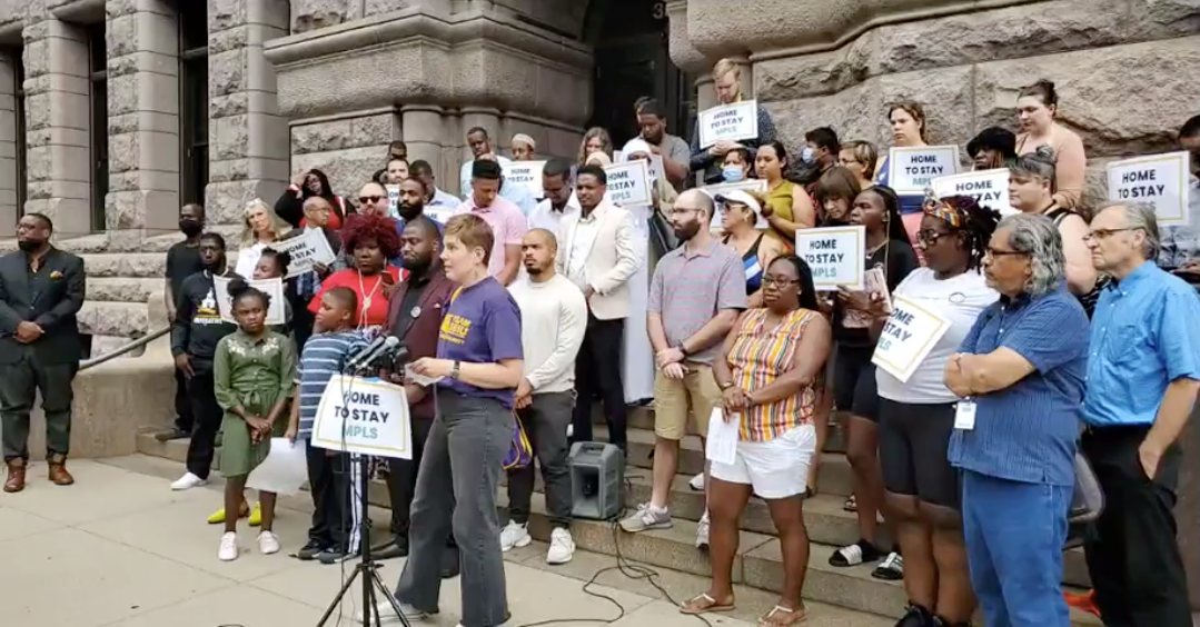 a large diverse group of people stand outside on the beige steps of city hall in front of a microphone set up