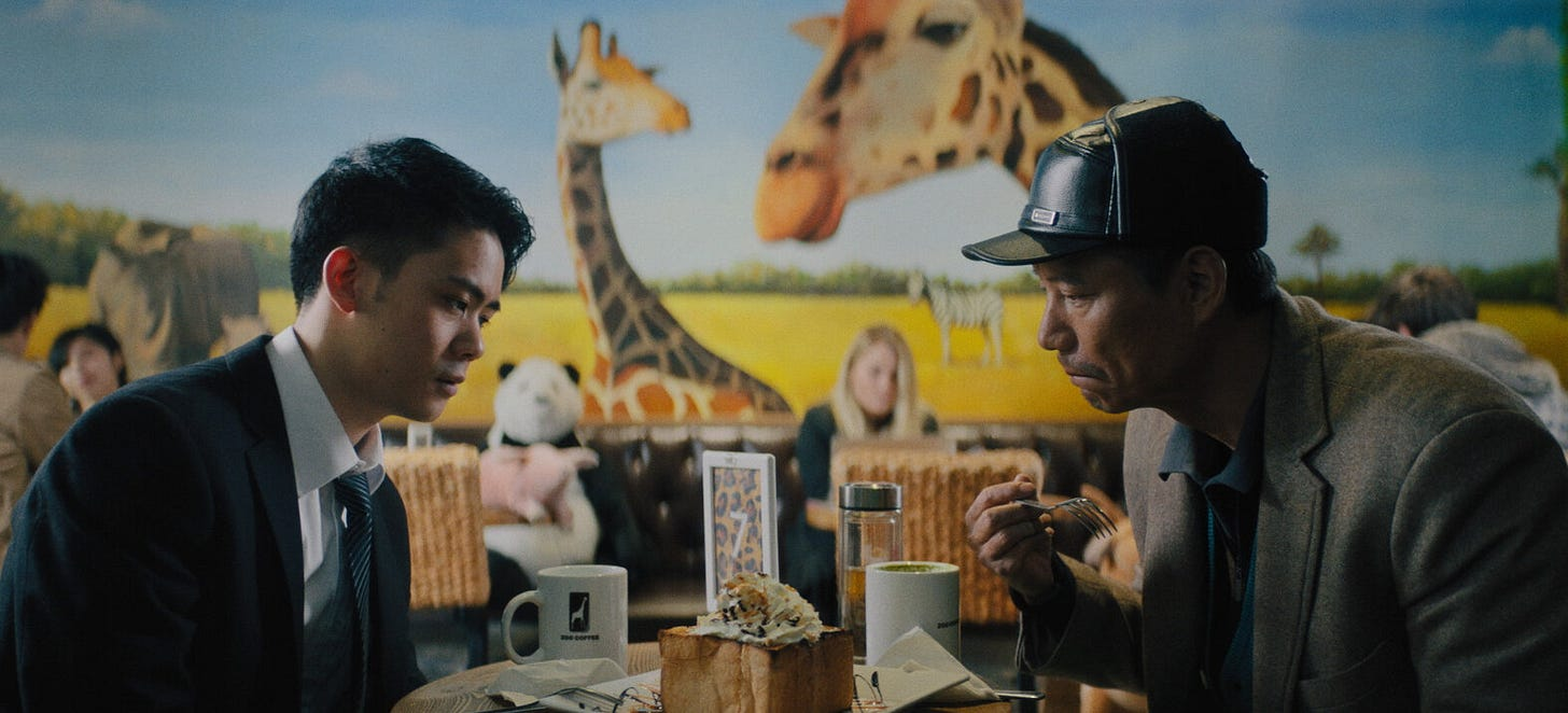 A father and grown son sit at a table and stare at a fancy cake between. The son on the left looks dejected, and the father on the right looks somewhat sullen but is raising his fork. Behind them people are dining and there's a giant giraffe mural on the wall.