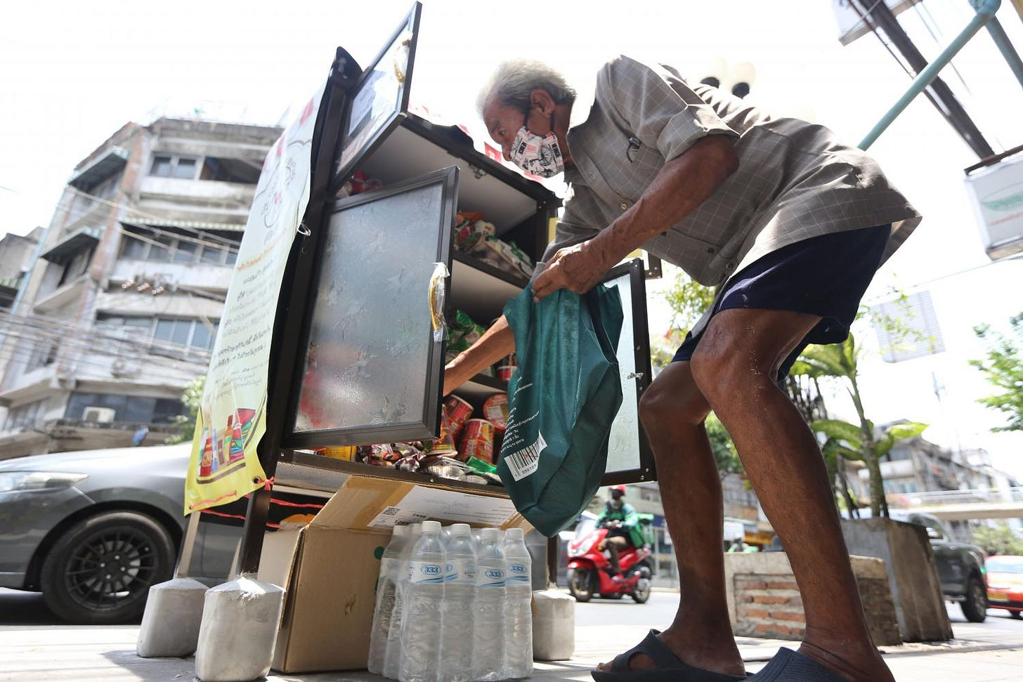 A man selects items he needs from a roadside cupboard on Sukhumvit 71.  Wichan Charoenkiatpakul