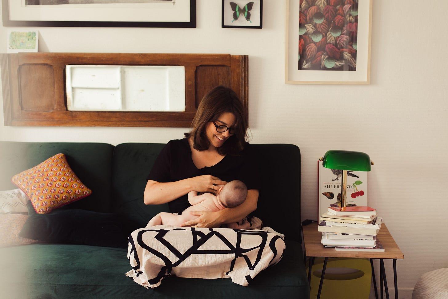 Une femme assise sur un canapé allaite un nourrisson. Elle le regarde en souriant.