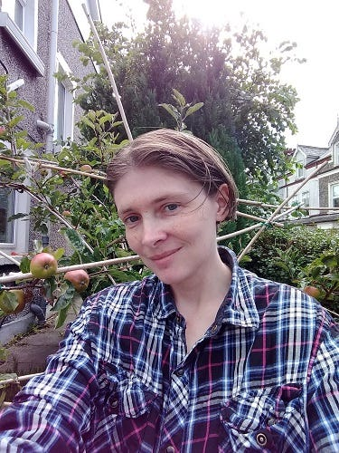 Portrait of Angeline B. Adams. She has short, light brown hair, blue eyes, and is wearing a blue plaid shirt. She is outdoors in front of an apple tree and some houses can be seen further in the background.
