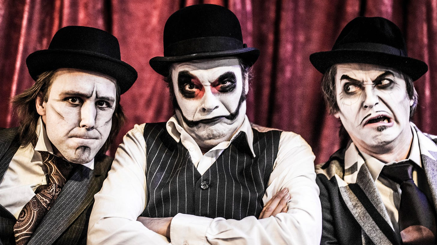 Three sinister men in bowler hats and whiteface snarl at the camera.