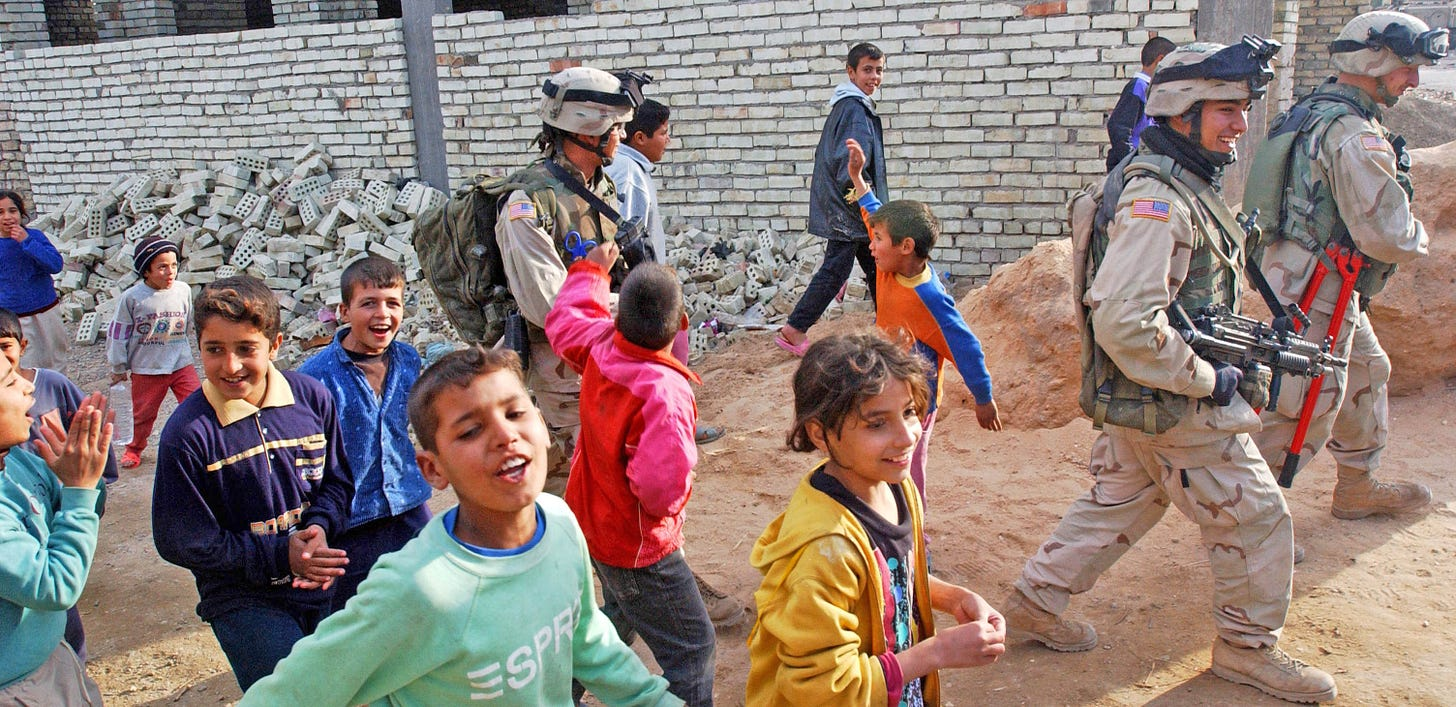 Three US Soldiers walk with children in the streets of Mamudiyah, Iraq, Dec. 30