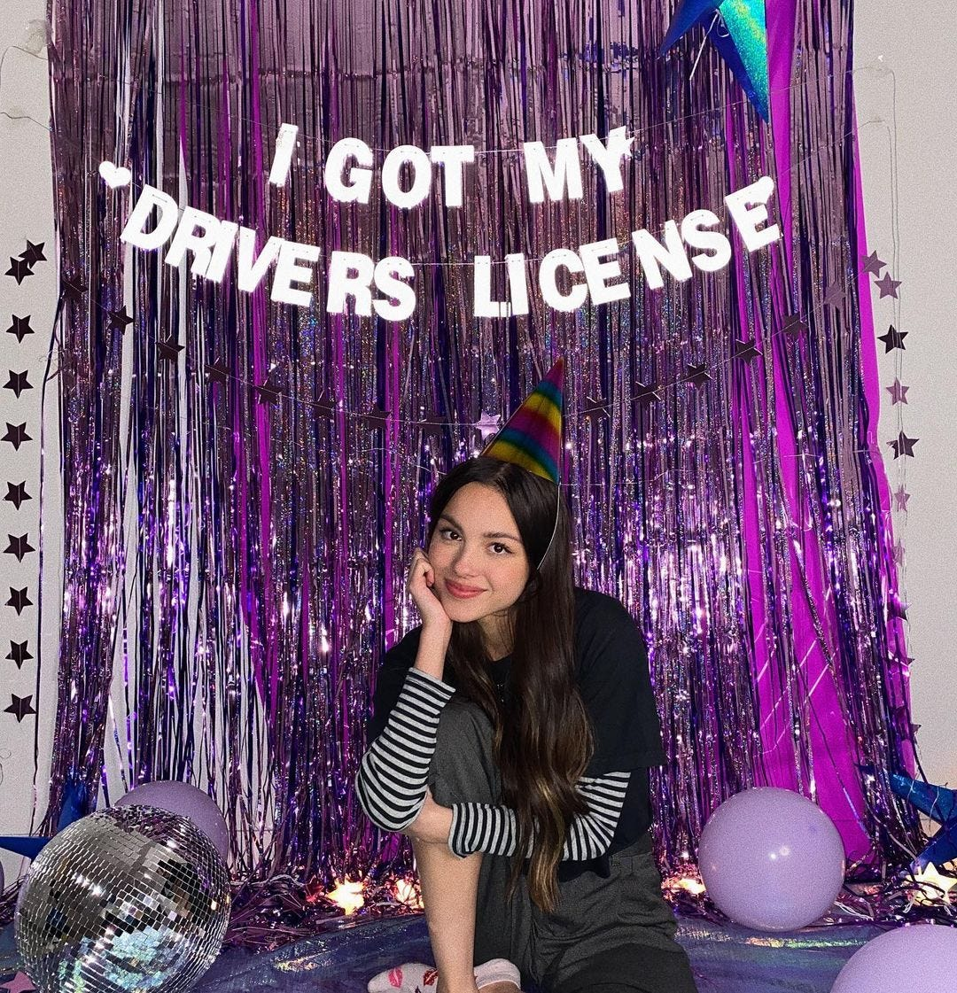"""Olivia Rodrigo in front of a wall that says """"I got my Drivers License"""""""