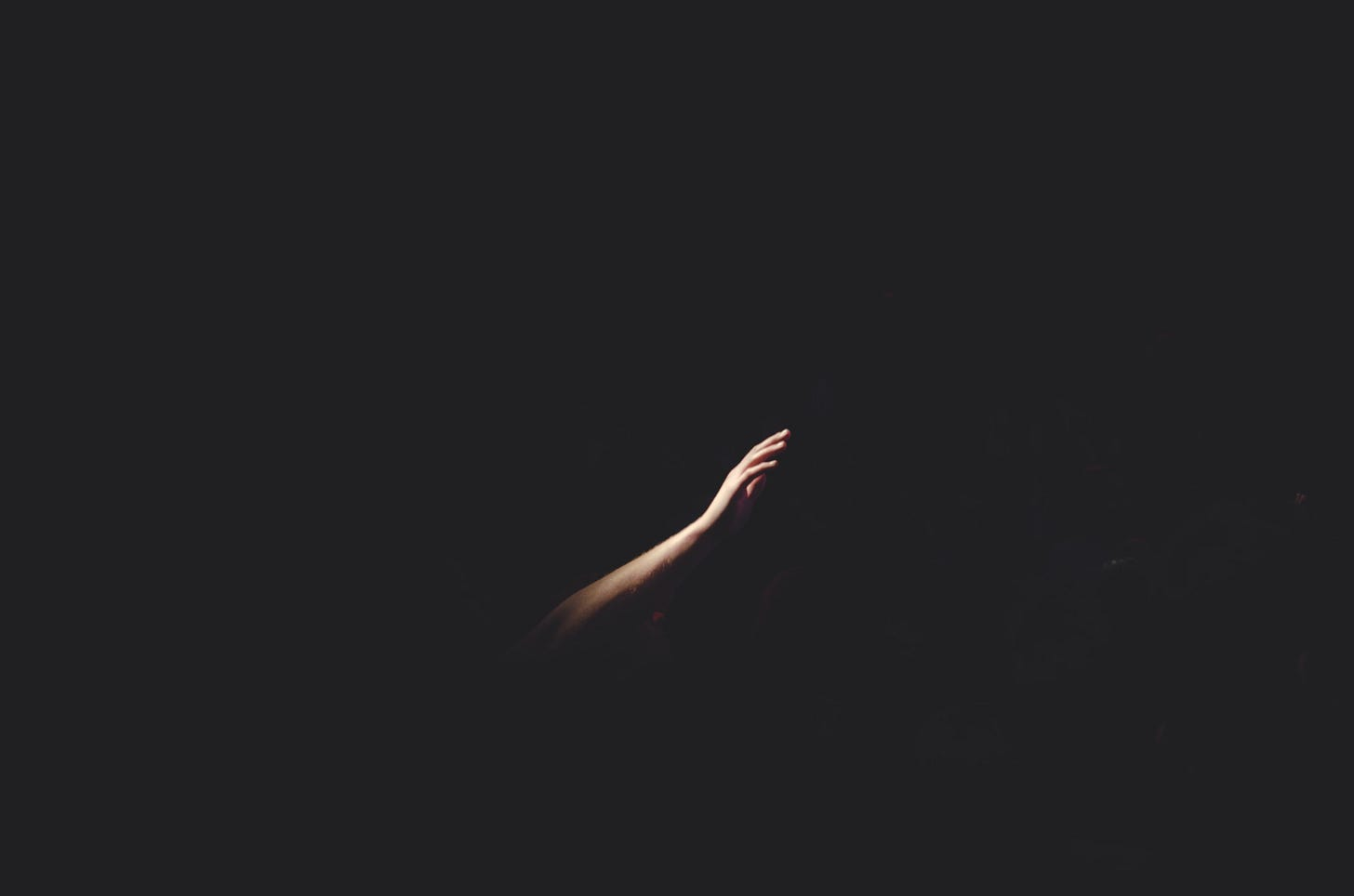arm reaching out in darkness