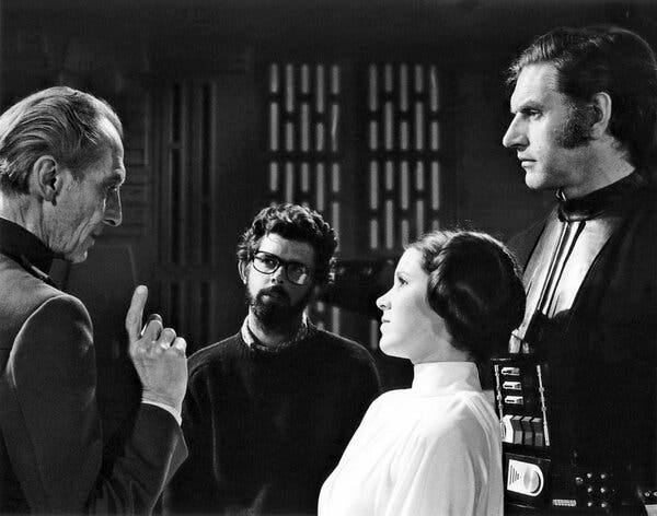 """From left, Peter Cushing, George Lucas, Carrie Fisher and Mr. Prowse on the set of the first """"Star Wars"""" movie, which was released in 1977."""