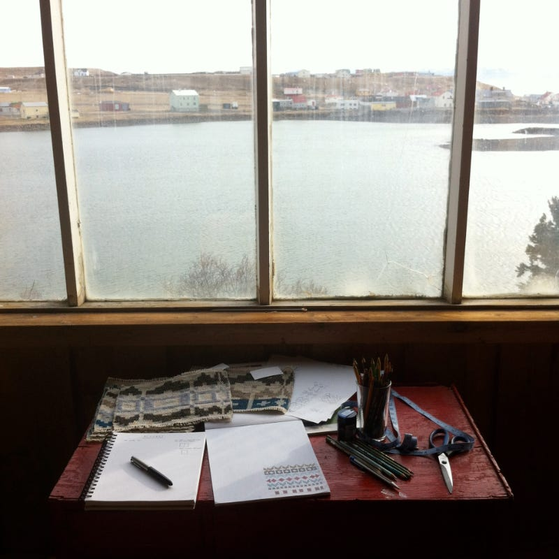 Desk with woven samples, notebook, pencils, scissors in front of a window looking out over a river
