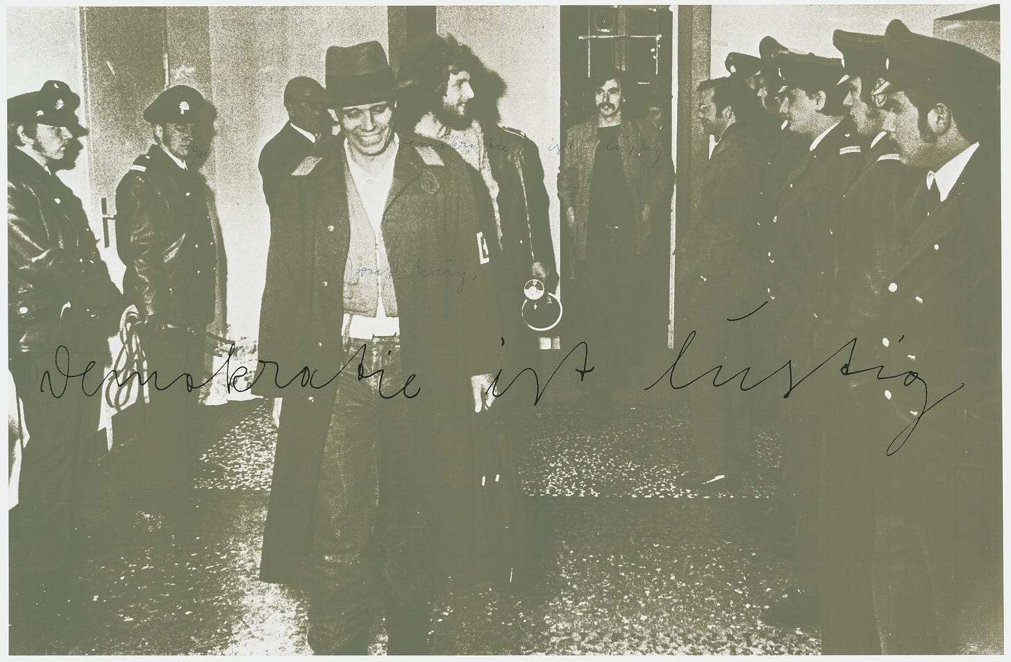 A black and white screenprinted photograph with a slight green tint. On top of the image are the words Demokratie ist lustig or Democracy is Merry. The photograph is of Joseph Beuys wearing a trench coat, jeans, and a fedora hat smirking as he is escorted from the Kunstakademia Düsseldorf where he was formerly employed as a teacher.