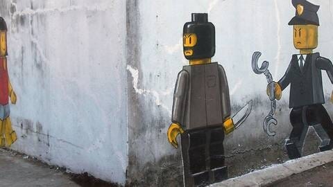 A Banksy like painting depicting a would-be masked Lego robber aiting around a corner for a potential female Lego victim, while a Lego policeman moves in for apprehension.