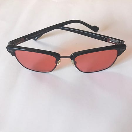 A still photo of Rachel Cassandra's migraine glasses, red-brown lens with black frames on a white background.