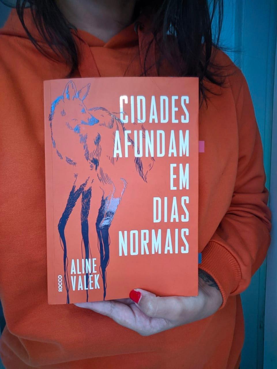 fotografia de uma leitora segurando o livro Cidades afundam em dias normais, usando um moletom laranja, cor de telha, no mesmo tom da cor da capa com a ilustração reluzente de um lobo-guará