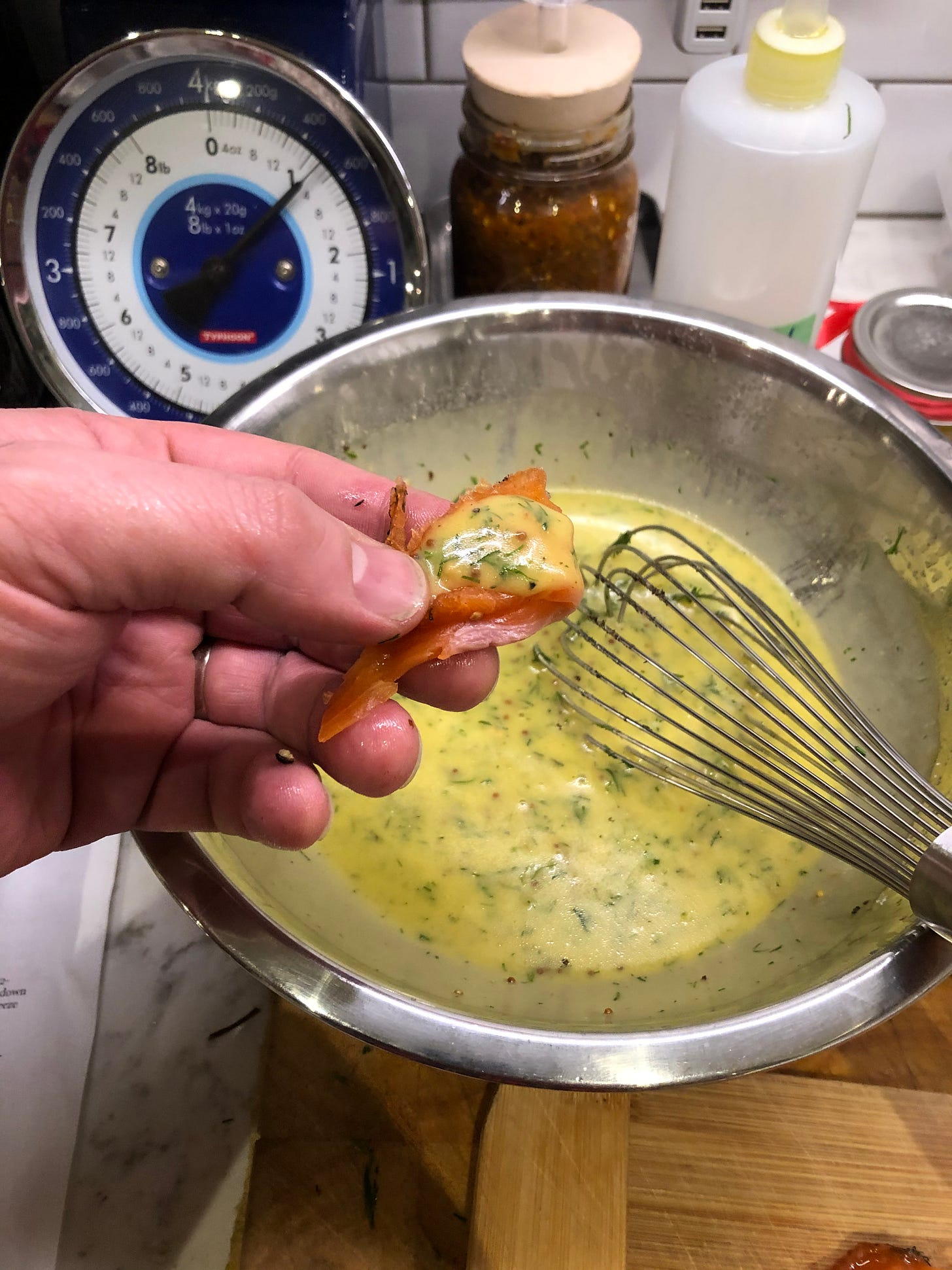 A thin slice of gravlax with a small dollop of mustard-dill sauce, being held over a mixing bowl of just-made sauce.