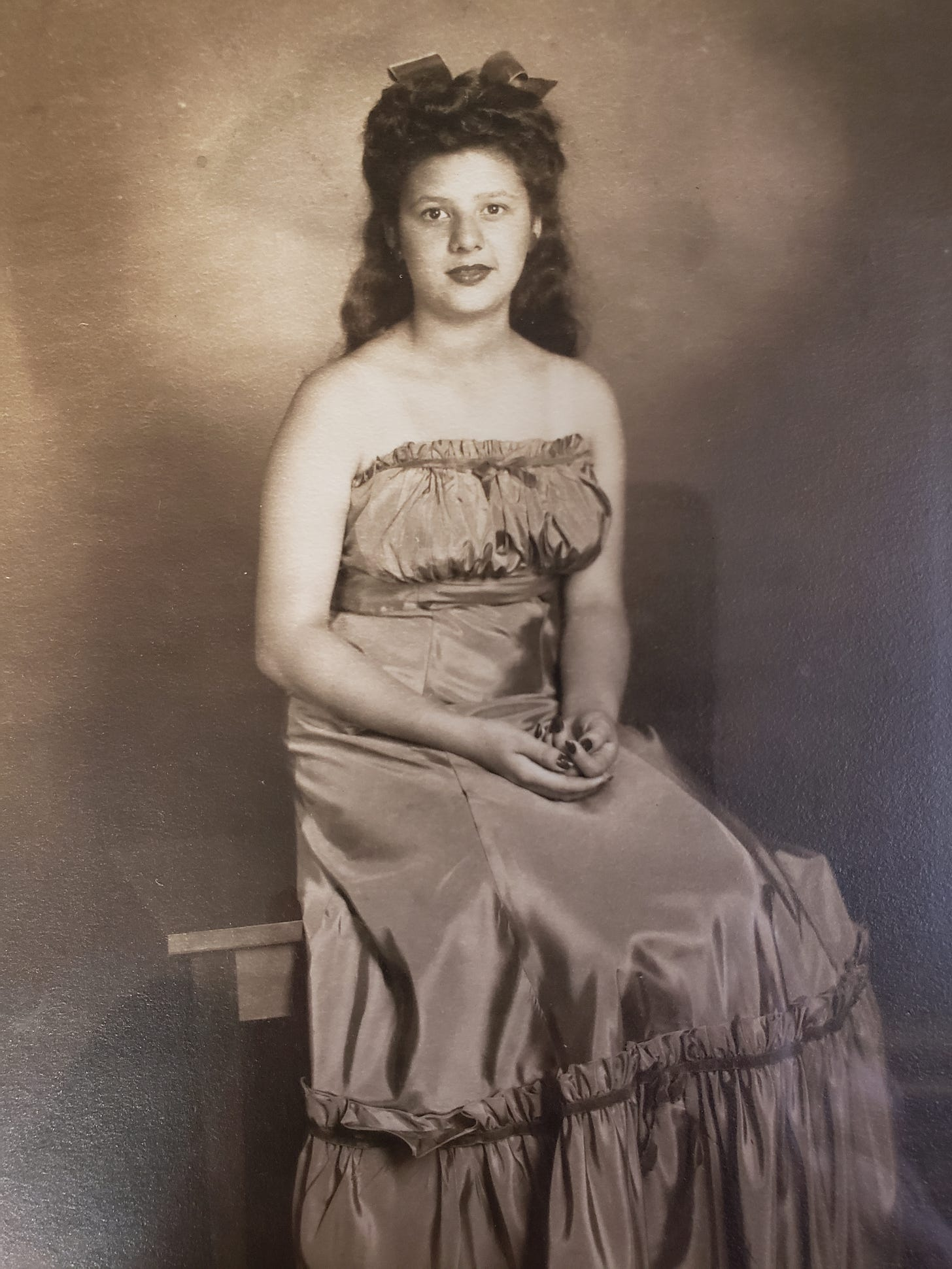 Photograph of Anita Juarez as a young woman, posing in a dress, seated, hands in lap