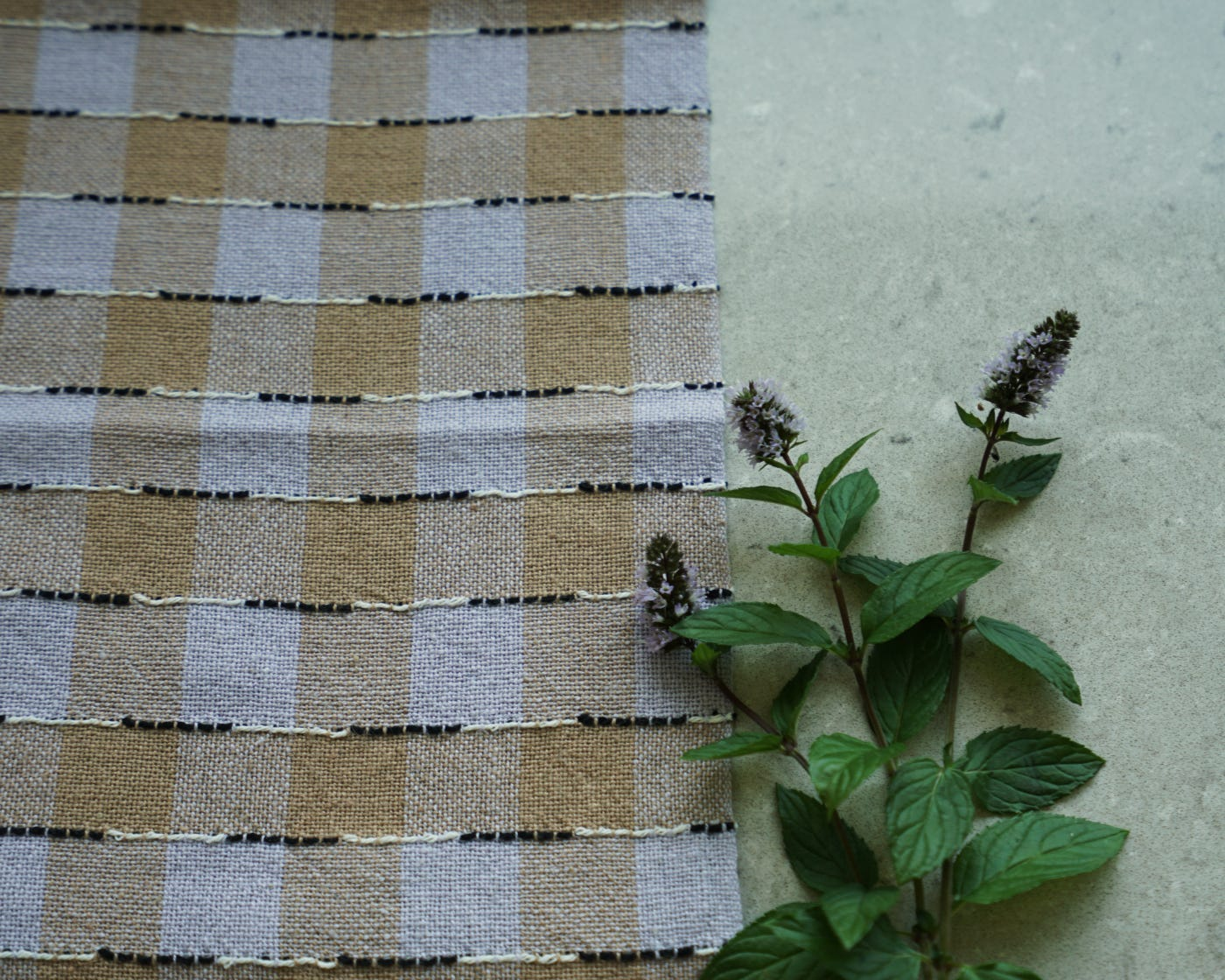 A flat cloth on a countertop with three flowering sprigs of mint