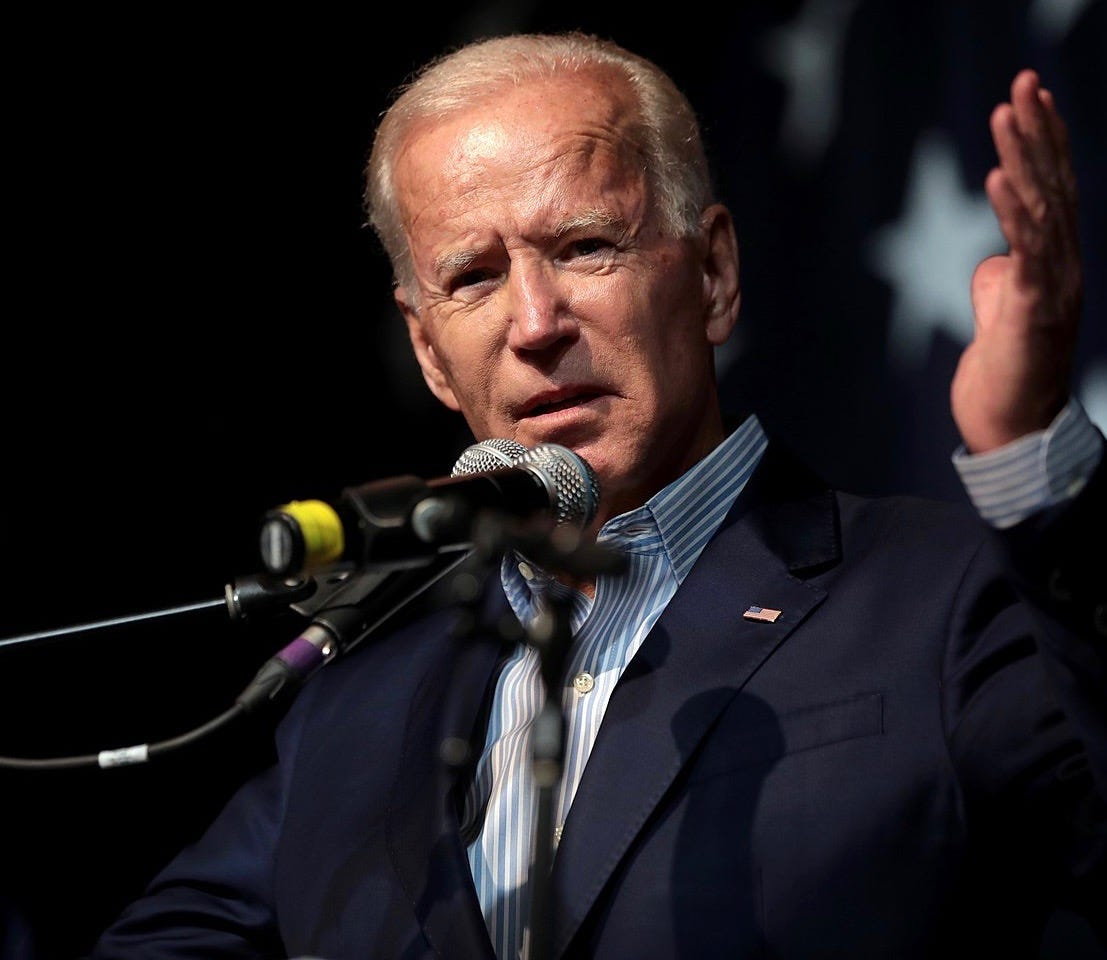 Joe Biden at a podium, with a serious expression and one hand raised to emphasize a point