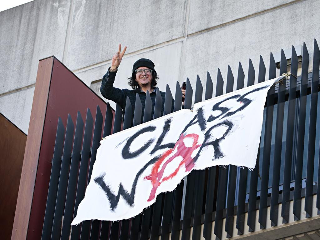 """A young anarchist smiles down from a balcony, holding up two fingers in a V above a banner that reads """"CLASS WAR"""" with the A for anarchy symbol."""