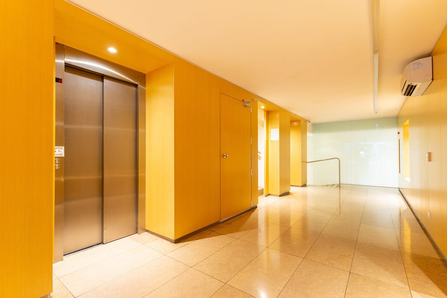 photo shoing doors of an elevator in a dark yellow corridor