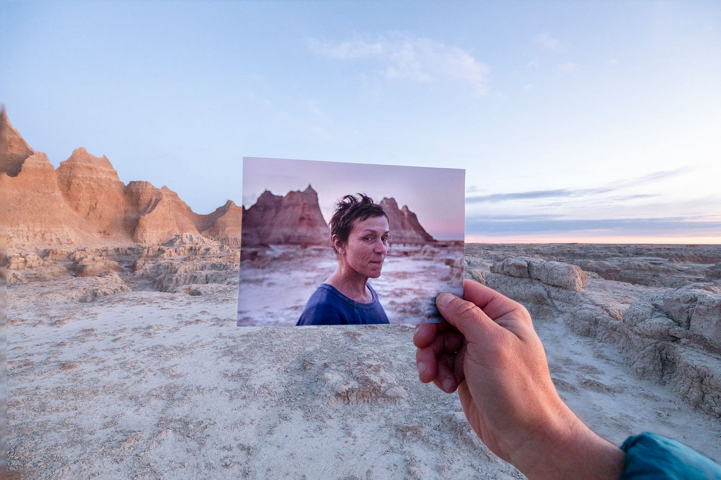 A person holding a picture in front of a desert.