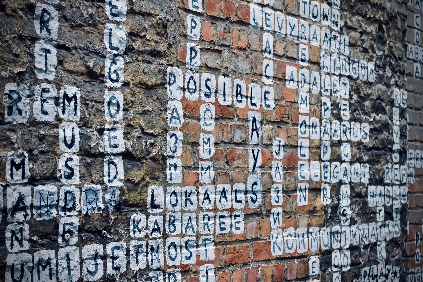 """Image of scrabble painted on a wall for article titled """"words just don't cut it"""" by Larry G. Maguire"""
