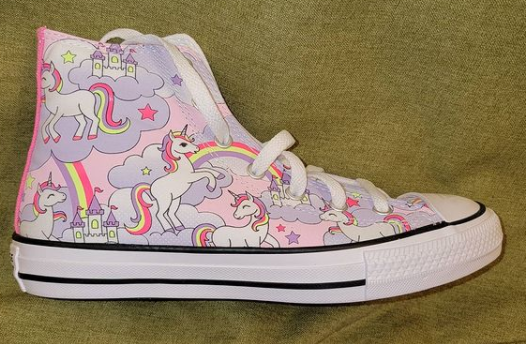 Image of single shoe. It is a high-top Converse shoe with a pink background, purple clouds, purple, pink, and neon yellow unicorns and rainbows and castles.