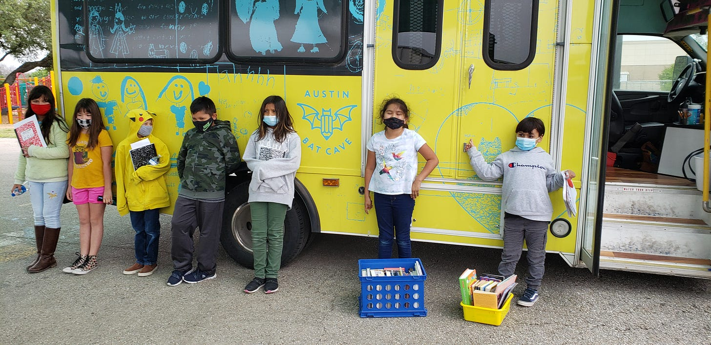 a group of masked students standing in front of the Bat Mobile's yellow side panel.