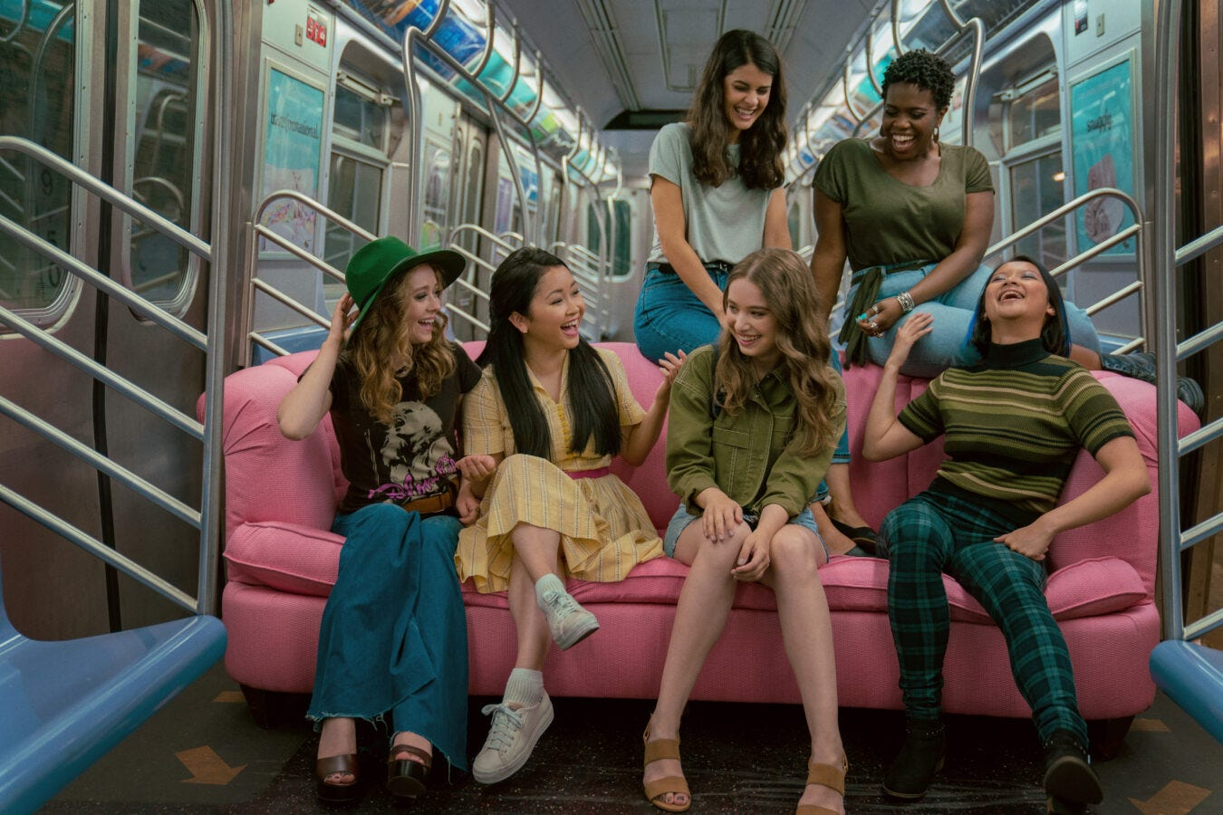 Still from To All the Boys: Always and Forever of the main character and her friends sitting on a pink couch on the subway. Two of them are sitting on the back and four are sitting on the couch.
