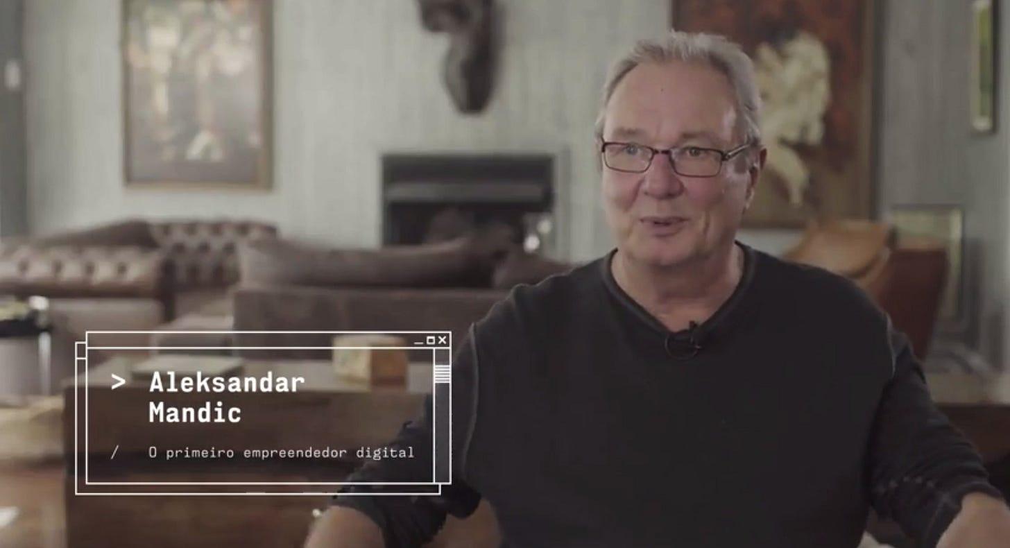 """Foto de Mandic, de moletom preto, óculos e cabelos grisalhos. Na legenda da foto, seu nome e a inscrição """"O primeiro empreendedor digital""""."""