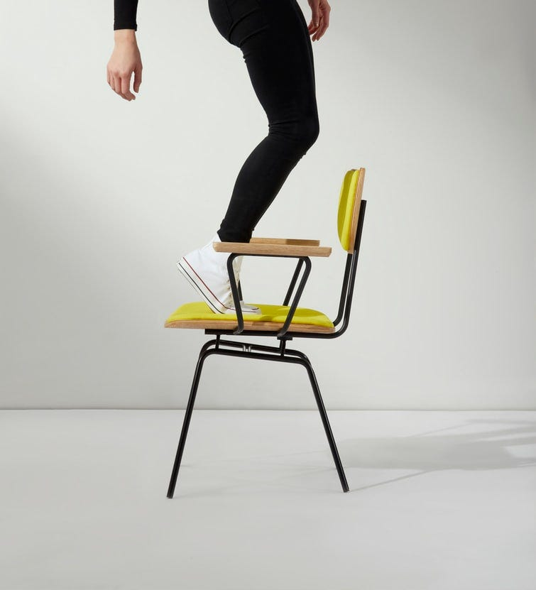A photo of a yellow chair in the center of the frame against a black background. There is a person standing on the seat of the chair in converse and dark leggings, balancing on their toes. Only the lower half of the person's body is visible.