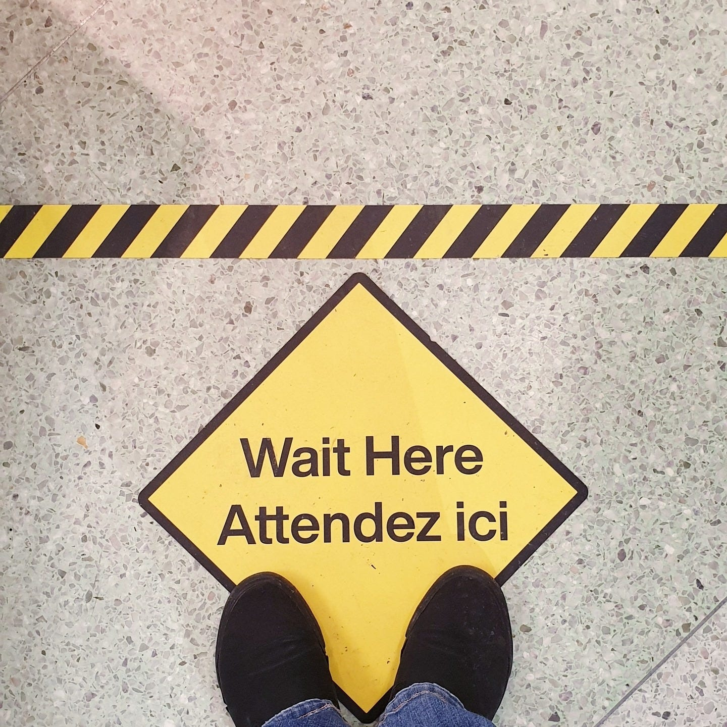 """A shot of the ground with a yellow tape to make the start of the queue line and a yellow rhombus with the phrase """"Wait here"""" in English and French."""