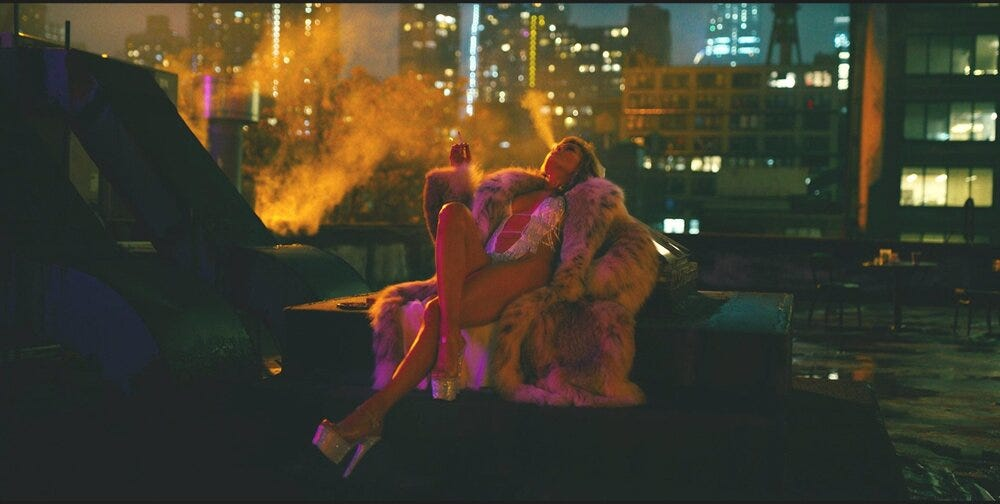 JLo lying resplendent on a roof in the film Hustlers. She's smoking a cigarette and blowing smoke into the air while wearing a silver leotard and enormous fur.