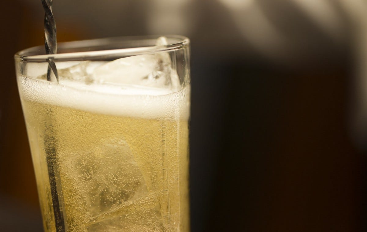 Closeup of a glass of a light-gold carbonated drink with ice and a metal stirrer.