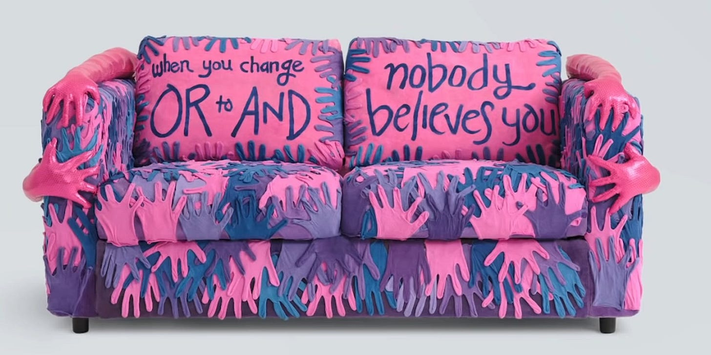 """A loveseat covered with hand shapes in blues, pinks and purples, with molded 3D hand sculptures on the arms. The back cushions read """"When you change OR to AND / nobody believes you."""""""