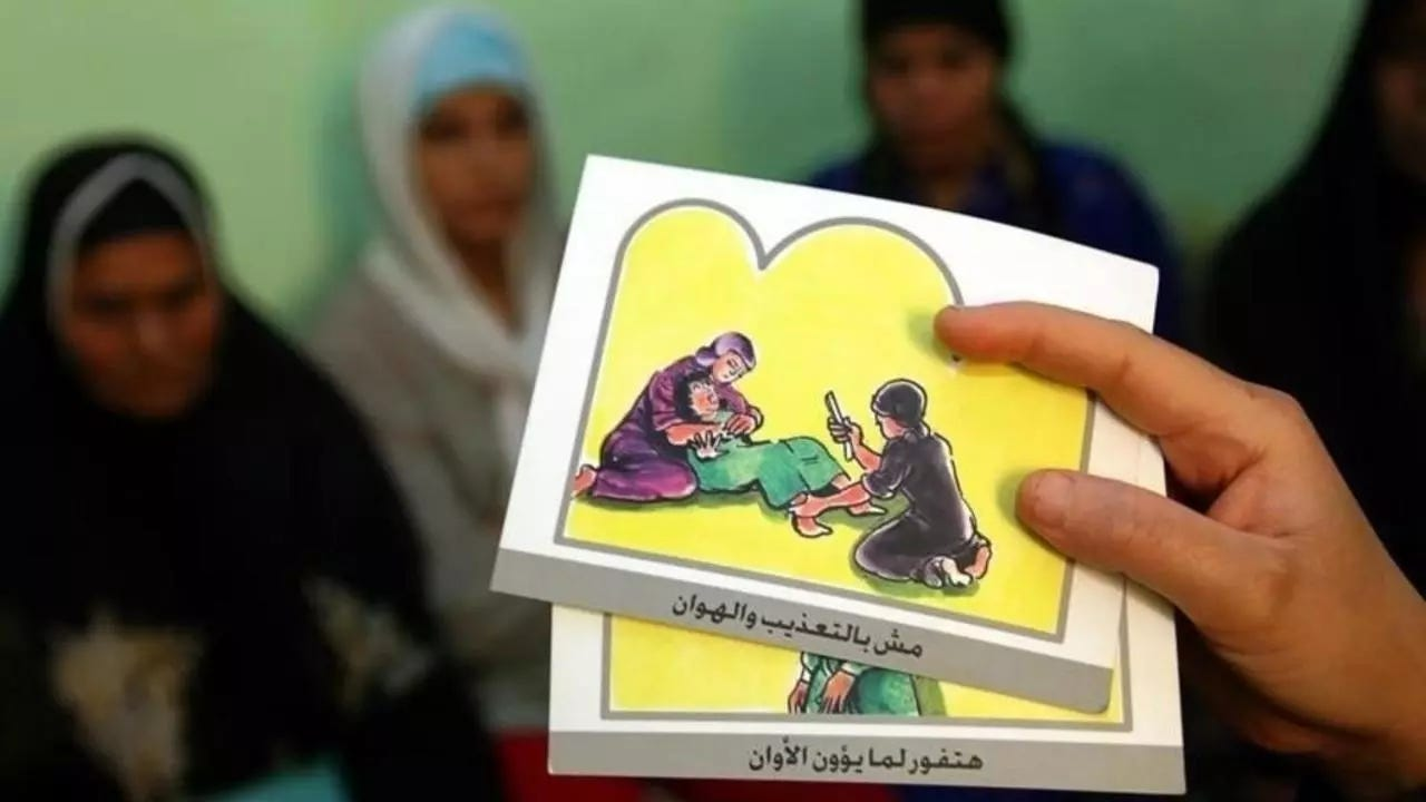 A counsellor holds up cards used to educate women about female genital mutilation (FGM) in Minia, Egypt, June 13, 2006. REUTERS / Stringer
