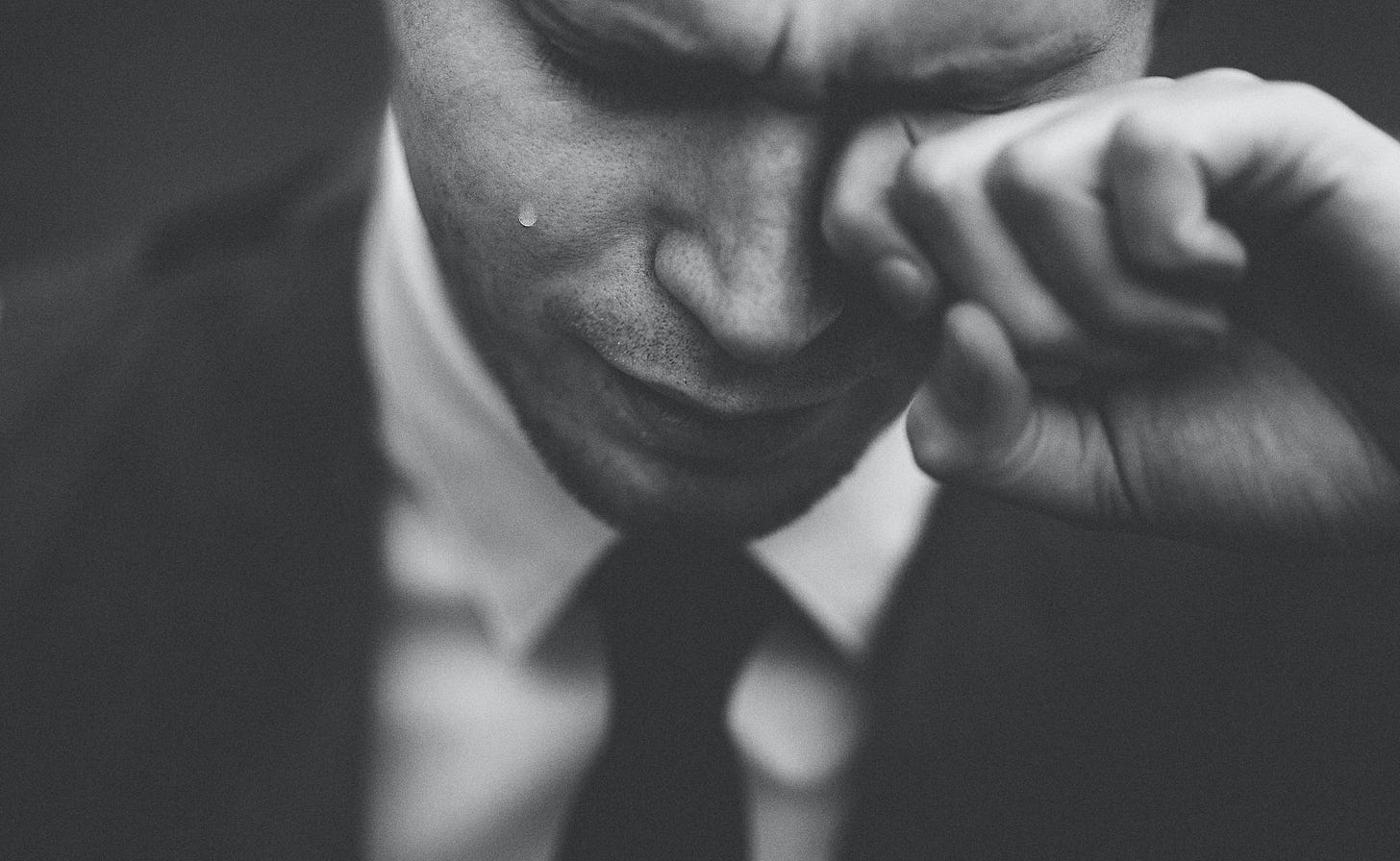 A man in a suit and tie crying.