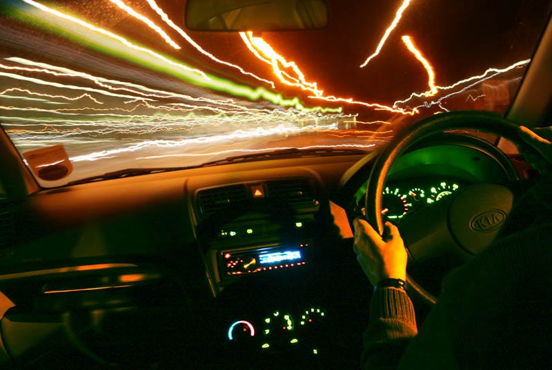 Image description: This is a color photo that depicts a driver in a car at night with their hand on the steering wheel as traffic lights glimmer in the distance.