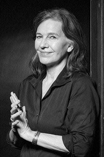Black & white portrait of Louise Erdrich from the waist up, taken at a slight angle. She is smiling like she has a secret.