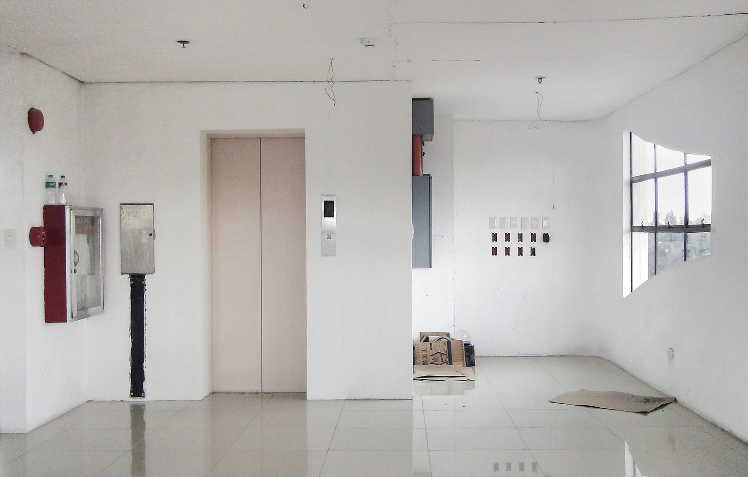 imagem mostra apartamento vazio, branco, com porta de elevador fechada.