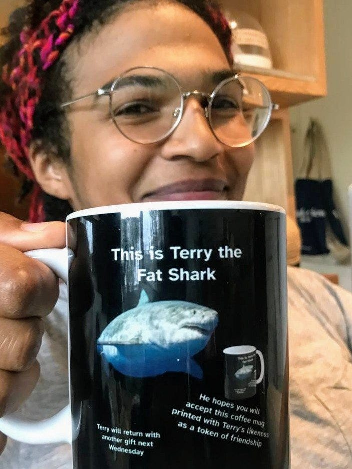 """Picture of Chigozie Nri smiling and holding up a coffee mug that says """"This is Terry the Fat Shark"""" above a picture of a shark that does indeed look portly. Below Terry it says """"He hopes you will accept this coffee mug printed with Terry's likeness as a token of friendship"""" and """"Terry will return with another gift next Wednesday."""" And incredibly, in front of Terry there is a picture of this very mug."""