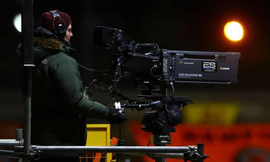 A TV cameraman films a sports event