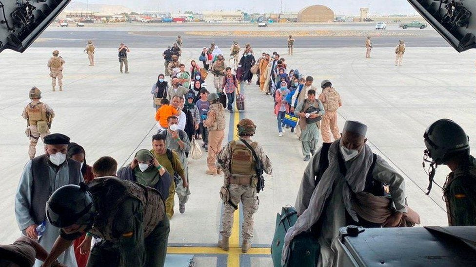 Afghans and Spanish citizens residing in Afghanistan board a military plane as part of their evacuation
