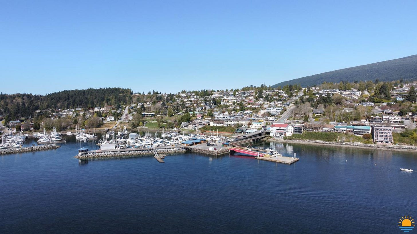 Drone photo of Gibsons Harbour as seen from the water. The surrounding town of Gibsons is in the background.