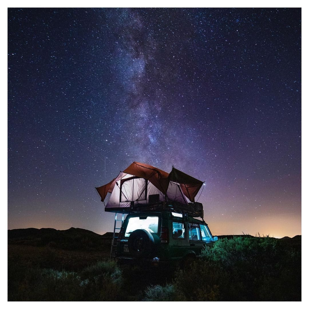 SUV with Rooftop tent at night under the stars