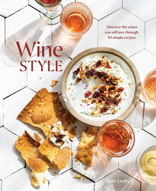 Cover for Kate Leahy's cookbook Wine Style; image is of a white tile background with multiple glasses of wine surrounding a ceramic bowl of white dip, topped with nuts, and several broken crackers.