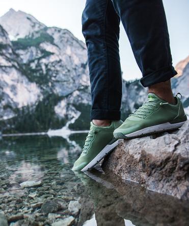 a man wears the tropicfeel canyon shoes into a mountain lake