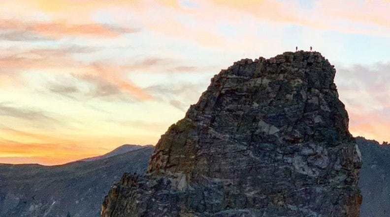 tommy caldwell and alex honnold standing on top of a huge mountain in colorado
