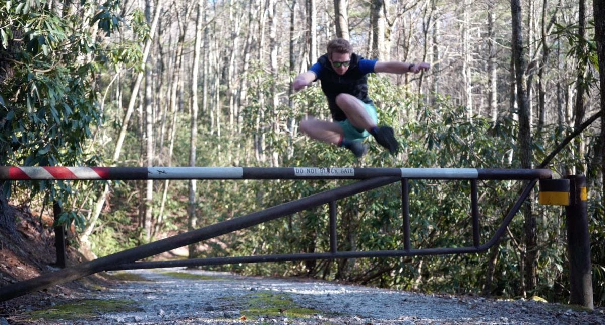 ryan jumps over a gate while trail running